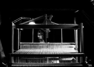 Artist Hanna Norrna sitting at her loom in the attic of Gathenhielmska Huset