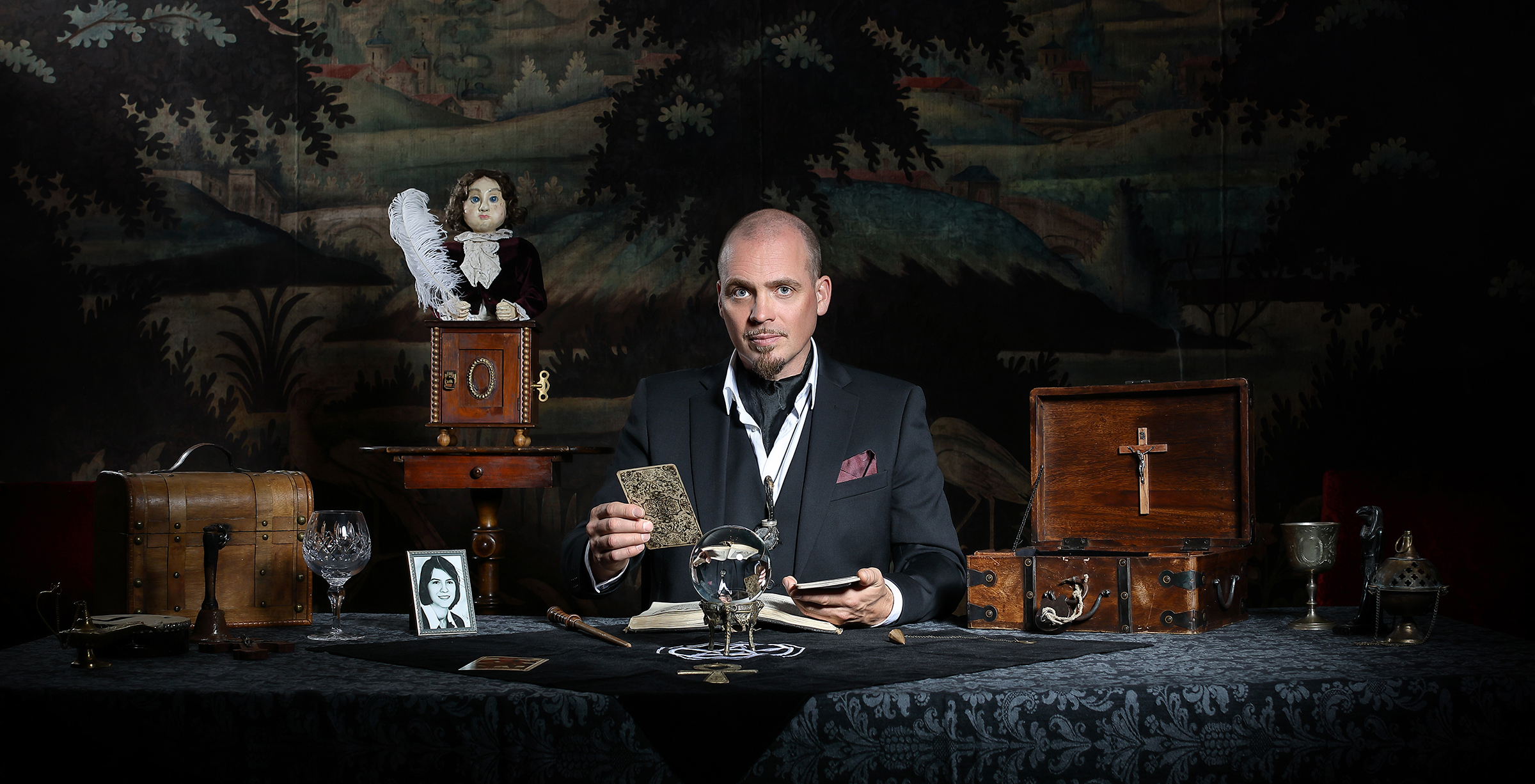 The artist Gaston, sitting a table with a selection of trinkets to either side. He is wearing a black suit and holding a tarot card.