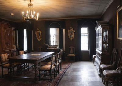 Kungasalen at Gathenhielmska Huset. The room features a wooden table, chairs, cabinets, mirrors and a portrait painting in a glass frame.