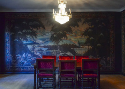A picture of Italiarummet at Gathenhielmska Huset. Six red chairs, a table and a chandelier. The tapestries on the walls are from Northern Italy and depict an island scene in blues and greens.