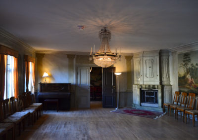 Salongen at Gathenhielmska Huset, with a chandelier, a piano, two lamps, chairs and tapestries on the wall.