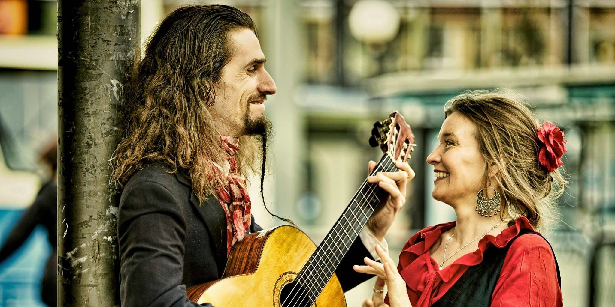 Marianne and Emil, laughing together. Emil is holding a guitar.