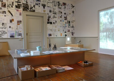 An exhibition in a room, featuring a selection of A3 prints on a wall, a table laid out with materials and two projector screens showing images