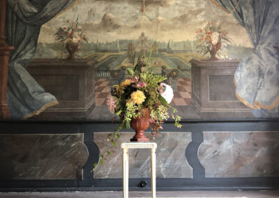 A bouquet of flowers in front of a wall tapestry