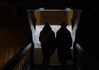 The backs of two people walking up a staircase