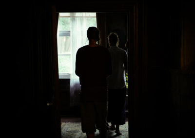 Two women walking into a dimly lit room