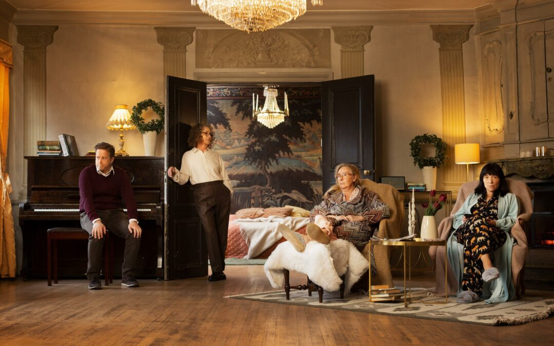 Four actors in a room, one in smart attire sat by a piano, one in smart attire leaning against a door, two in bedclothes sat in armchairs